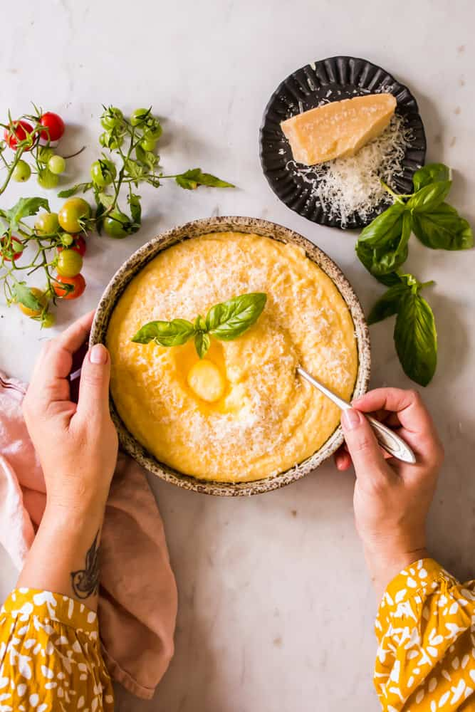 womans hands holding a brown bowl filled with creamy yellow polenta