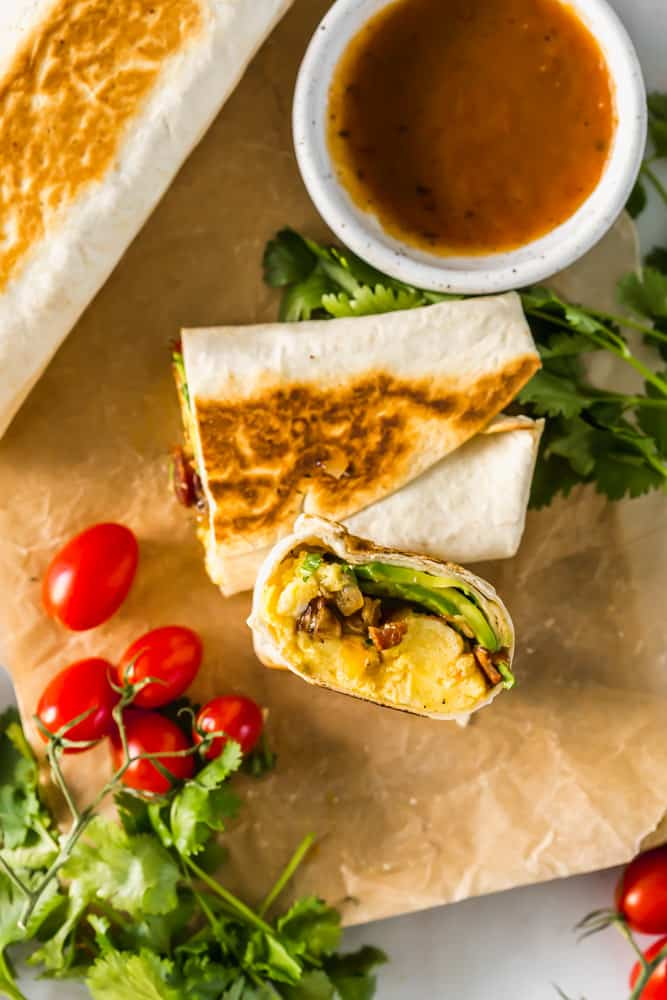 showing the inside of a halved breakfast burrito on parchment paper