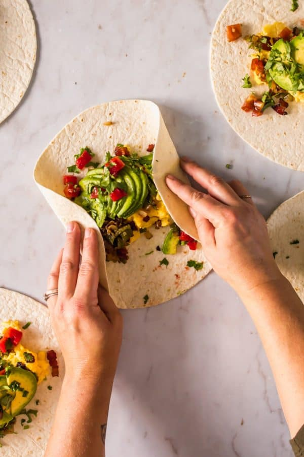 womans hands wrapping a tortilla around filling in the middle