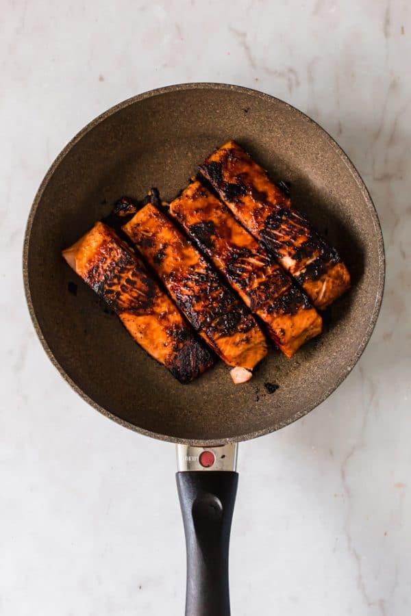 cooking 4 salmon filets in a metal pan.