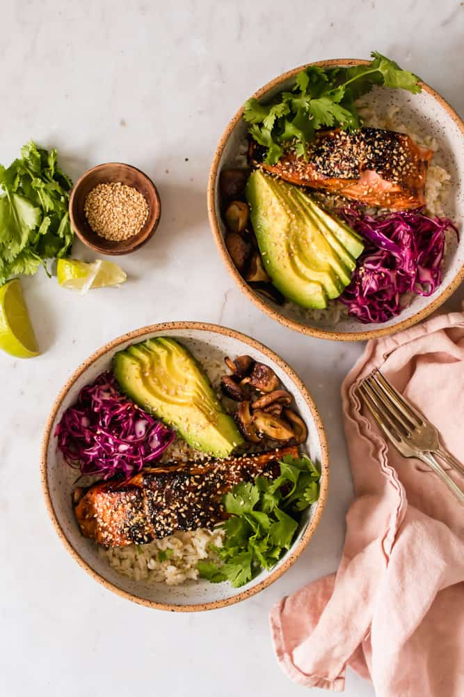 2 white bowls filled with cooked salmon filets, rice, avocado, purple cabbage, mushrooms, and green cilantro.