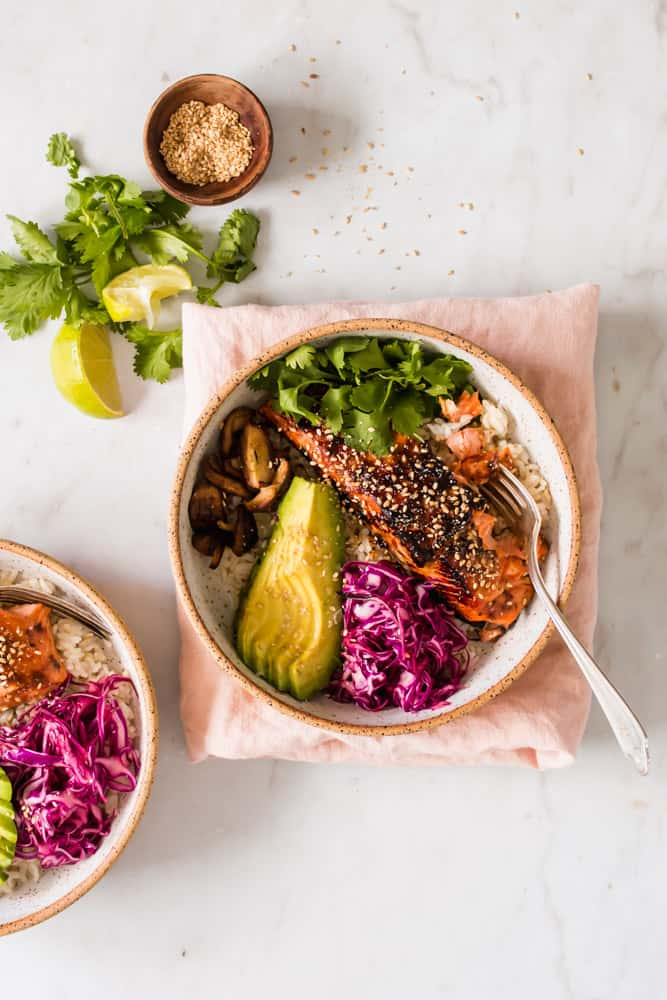 A white bowl filled with cooked salmon filet, rice, avocado, purple cabbage, mushrooms, and green cilantro sitting on a pink towel.