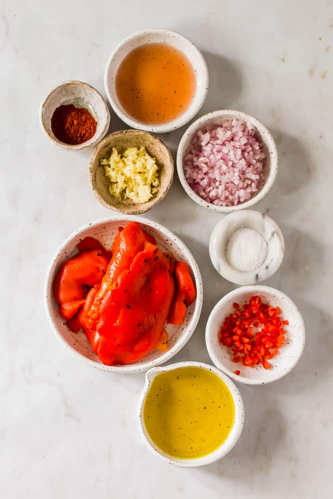 small white bowls filled with red peppers, chopped onion and garlic, oil, and spices.