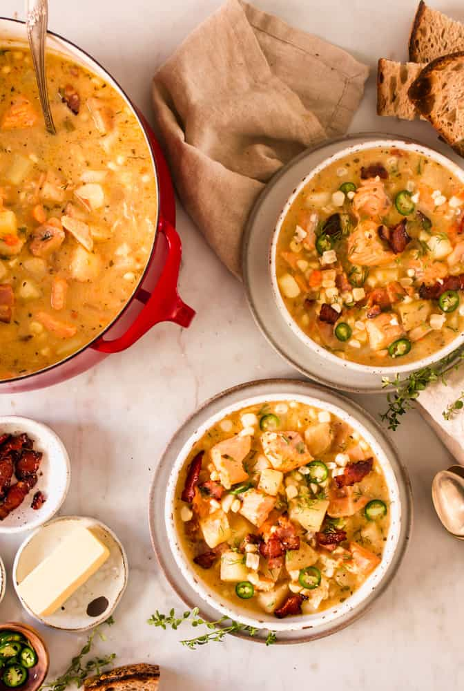 large red pot next to 2 white bowls filled with soup loaded with chunks of salmon, potatoes, bacon, and veggies.