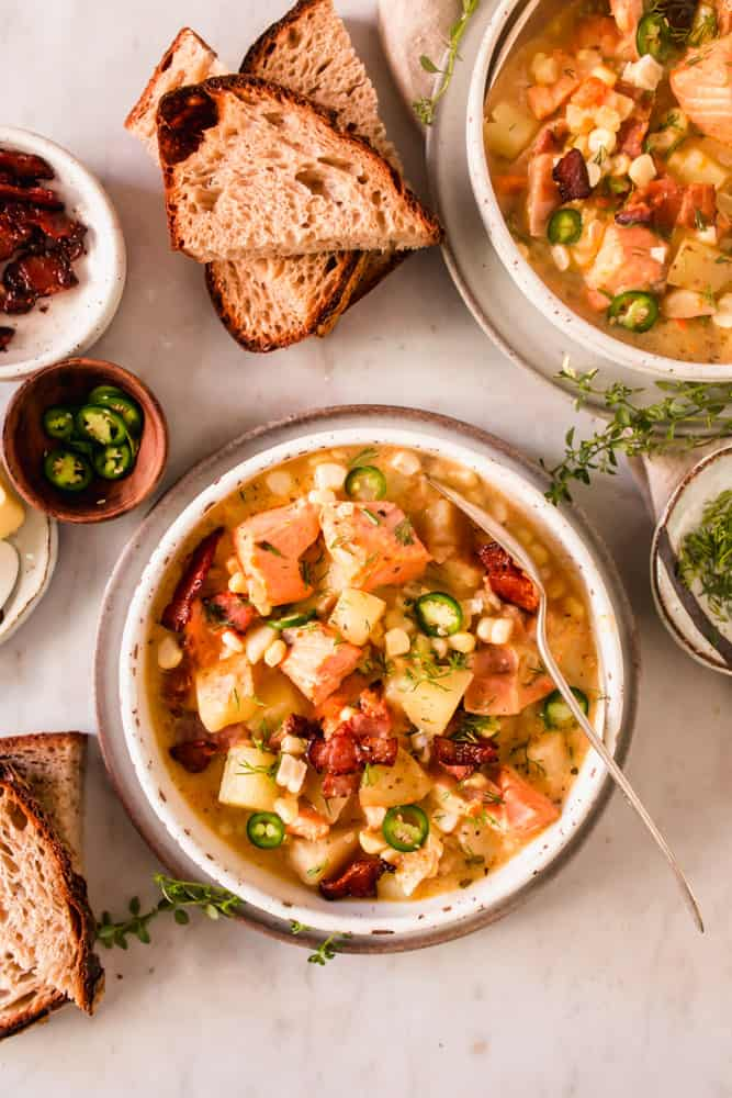 2 white bowls filled with soup loaded with chunks of salmon, potatoes, bacon, and veggies.