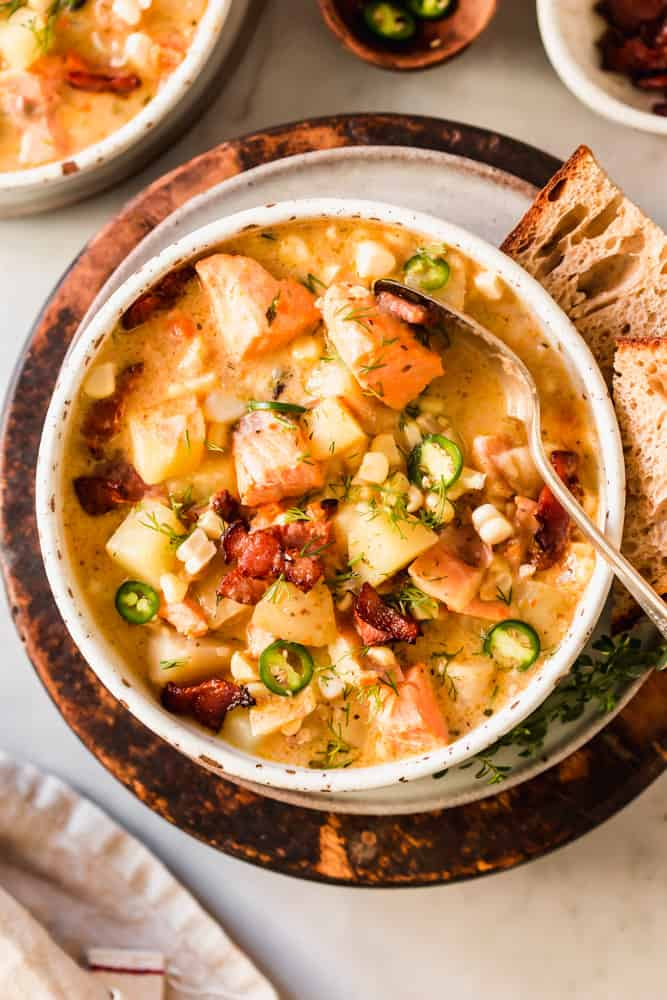 white bowl filled with soup loaded with chunks of salmon, potatoes, bacon, and veggies.