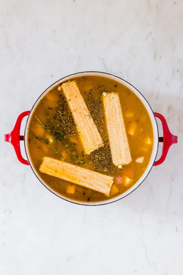 cooking corn cobs and vegetables in a large red pot.