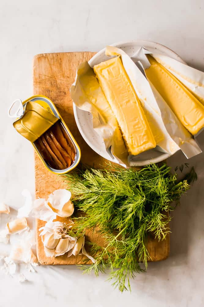 sticks of butter, fresh dill, raw garlic, and anchovies in a tin sitting on a wood board.